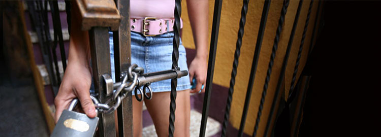Image of young woman behind a chained gate
